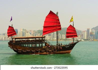 HONG KONG - APRIL 16, 2015: sailboat across Victoria Harbour. Victoria Harbour is a natural landform harbour situated between Hong Kong Island and Kowloon in Hong Kong.