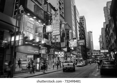 HONG KONG - AUGUST 4, 2016: City center with famous street view, parked cars, numerous shops, cafes and restaurants. Downtown during the cloudy day in Hong Kong. Black and white