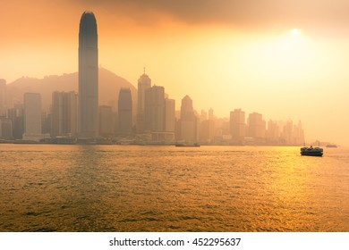 Hong Kong business district with sunset and sailing boat.