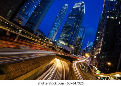 Hong Kong Central business district at the blue hour after sunset with light trails of busy road traffic and tall skyscrapers in the background.