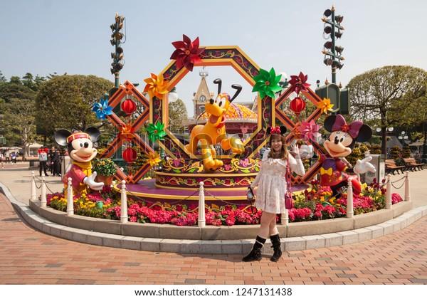Hong Kong, China, 10 February 2018 : A young woman posing in Hong Kong Disneyland view during winter