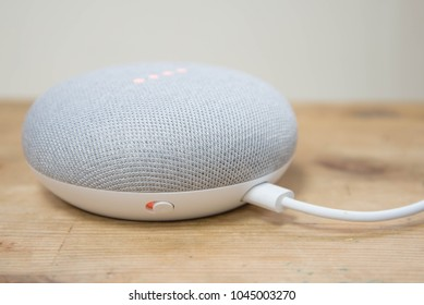 Hong Kong, China - 11 March, 2018: Physical microphone switch button of the Google Home Mini (Chalk color) on a wooden surface, orange LED turns on when mic off.