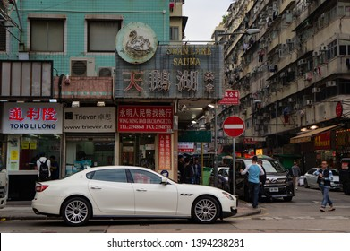 Hong Kong, China - 15/01/2019: The rich meets the poor. A luxurious Maserati Quattroporte parking in the poor district of Hong Kong, Sham Shui Po. Contrast of a limousine in front of rundown houses.