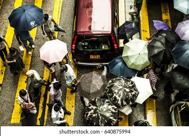 Hong Kong, China - 16 July, 2013: Top view of people crossing a street in the rain with many umbrellas