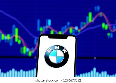 Hong Kong, China - 28 December 2018: BMW logo is seen on an smartphone over stock chart