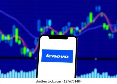 Hong Kong, China - 28 December 2018: Lenovo logo is seen on an smartphone over stock chart