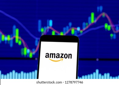 Hong Kong, China - 28 December 2018:  amazon logo is seen on an smartphone over stock chart