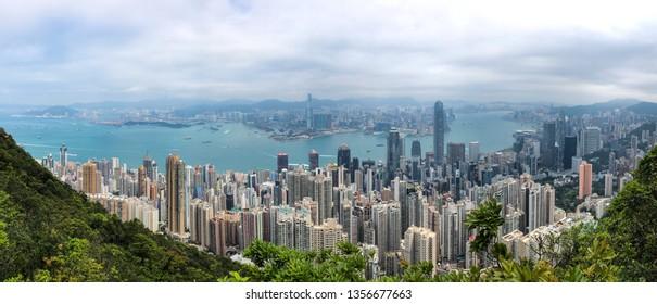 HONG KONG, CHINA - APRIL 2, 2019: Panoramic view of Hong Kong taken from Lugard Road viewpoint at Victoria Peak during cloudy afternoon.