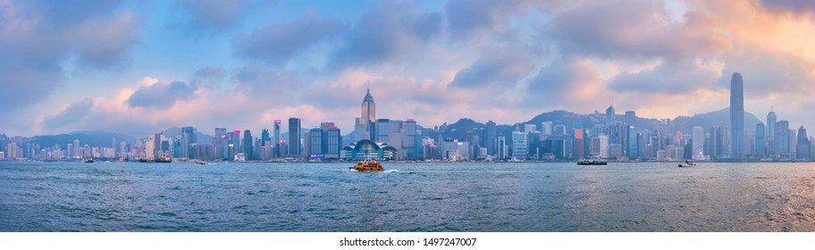 HONG KONG, CHINA - APRIL 28, 2018: Hong Kong skyline cityscape downtown skyscrapers over Victoria Harbour in the evening on sunset with junk tourist boat ferries . Hong Kong, China