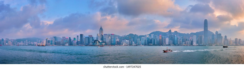 HONG KONG, CHINA - APRIL 28, 2018: Panorama of Hong Kong skyline cityscape downtown skyscrapers over Victoria Harbour in the evening on sunset with junk tourist boat ferries . Hong Kong, China