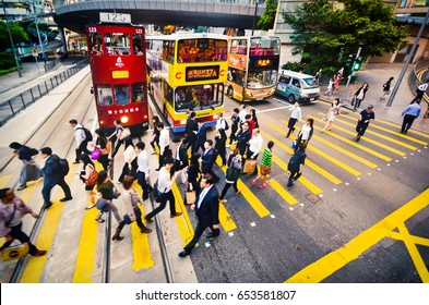 HONG KONG, CHINA - APRIL 29, 2014: A crowd of people in business suits cross the road on a pedestrian crossing. View from above. The effect of motion. Selective focus
