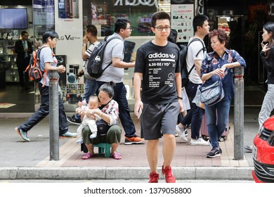 Hong Kong / China - April 9th 2019: A lady is sitting at the street side her child waiting for someone.