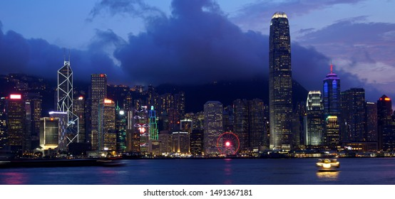 Hong Kong, China - August 12, 2019: Hong Kong skyline cityscape downtown skyscrapers over Victoria Harbour in the evening. Hong Kong, China
