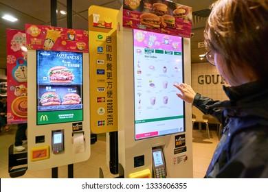 HONG KONG, CHINA - CIRCA JANUARY, 2019: woman use self-ordering kiosk in McDonald's restaurant in Hong Kong.