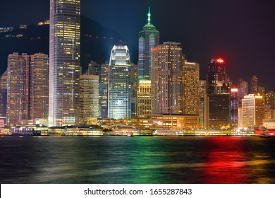 HONG KONG, CHINA - CIRCA JANUARY, 2019: view of the Central Ferry Piers and IFC mall with Central District in the background as seen from Victoria Harbour at twilight.