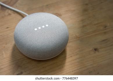 HONG KONG, CHINA - Dec 13 : Google Home Mini (Chalk color) on wooden desk background, the voice recognition streaming device utilizing Google Assistant from Google on Dec 13, 2017 in HONG KONG, CHINA.
