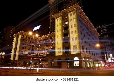Hong Kong, China - December 19, 2015: Night view of Hong Kong street with lights of traffic at long exposure and famous Peninsula Hotel in Kowloon built in 1928