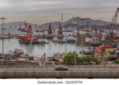 Hong Kong, China - December 21, 2015: Container ships at sea port Terminals and bridge with car in Hong Kong