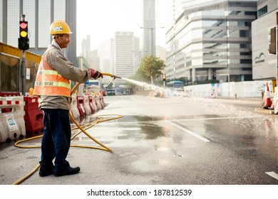 HONG KONG, CHINA - DECEMBER 22, 2013: Man cleaning road on December 22, 2013 in Hong Kong, China.