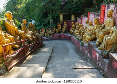 Hong Kong, China / December 26, 2018: istoric Statues Lining Walkway to Buddhist Hilltop Temple. Gold Statues of Arhat Buddha Monks along Path to the Ten Thousand Buddhas Monastery.