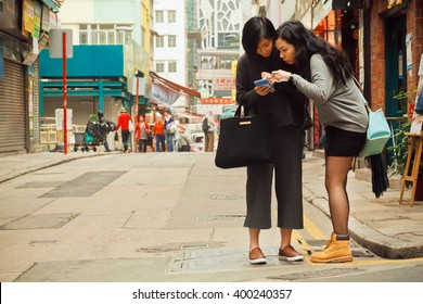 HONG KONG, CHINA - FEB 12: Two women watching cell phone to find way in big city on February 12, 2016. There are 1,223 skyscrapers in Hong Kong.
