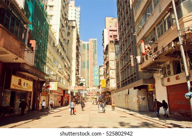 HONG KONG, CHINA - FEB 7: People walking on sunny street with tall concrete buildings in busy district of asian city on February 7, 2016. There are 1,223 skyscrapers in Hong Kong.
