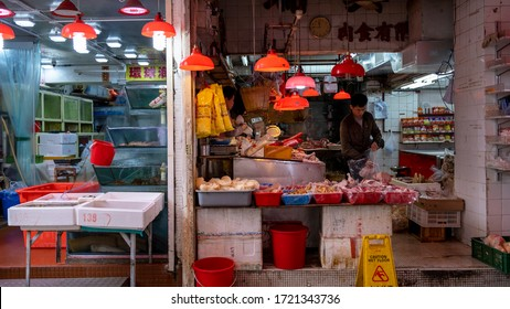 Hong Kong, China – February 25, 2019: A man and women are working in their wet market stall selling chicken meat. The red lamps make the meat look fresh.