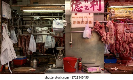 Hong Kong, China – February 25, 2019: An open air butcher, selling fresh meat at a market street stall in Hong Kong city, raw meat is hanging on hooks, front view of shop.