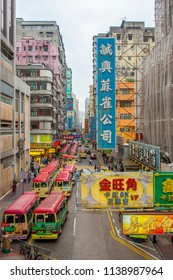 HONG KONG, CHINA - JAN 7, 2010: view to a shopping street in downtown Kowloon. Red busses wait for passengers.