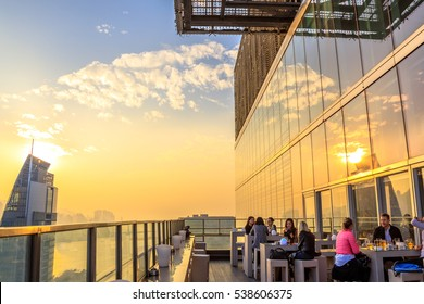 Hong Kong, China - January 1, 2016: people drink and enjoy the skyline of Victoria Harbor at sunset from the rooftop of Eye Bar, inside iSquare shopping center on Nathan Road in Tsim Sha Tsui, Kowloon