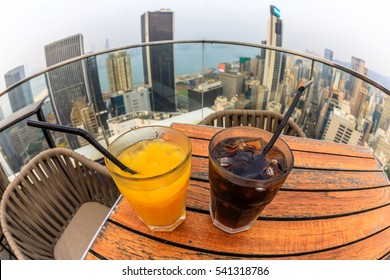 Hong Kong, China - January 1, 2016: cocktail with city skyline view at dusk from the rooftop of The Hennessy skybar in Wan Chai. fisheye angle of coke and juice close up.