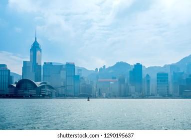 HONG KONG, CHINA - JANUARY 20 : Landmark skyscraper buildings at Victoria harbor with daylight mist, Hong Kong, China, on January 20, 2018.