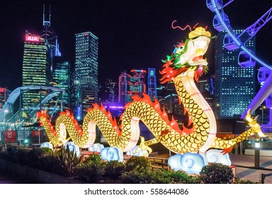Hong Kong, China - January 25, 2016: Big illuminated Chinese dragon figure festive outdoor decoration adorns the waterfront area in Central District. Night view with skyscrapers on background.