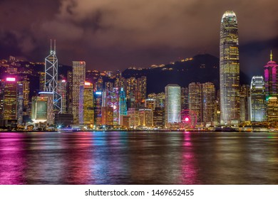 HONG KONG, CHINA - JULY 25, 2019: Hong Kong Victoria Harbour illuminated cityscape at night and water reflections.