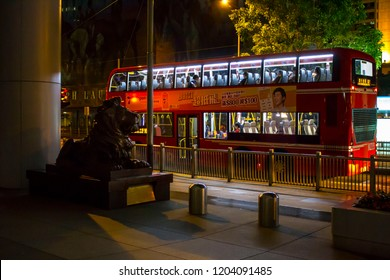 Hong Kong, China - July 27 2018: Red british doubledecker bus and bronze sculptures of Stephen and Stitt lions in front of HSBC building, situated in Central, Hong Kong.