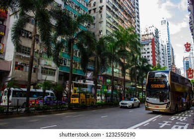 Hong Kong, China - July 27 2018: Traffic with doubledecker buses on the streets of Wan Chai. Palm trees, high rise residential and office buildings on Hennessy Road, Wan Chai district, Hong Kong.
