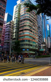 Hong Kong, China - July 27 2018: Old high-rise residential buildings alongside with modern skyscrapers at Hennessy Road, Wan Chai, with bright blue sky on the background. Busy crossroad at Wan Chai.