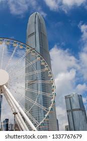Hong Kong, China, July 31, 2018:City under the blue sky white cloud ferris wheel