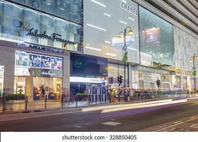 Hong Kong, China - June 13, 2015: Communters or shoppers waiting to cross the Canton Road with luxury brand stores in Hong Kong at night.