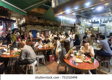 HONG KONG, CHINA - JUNE 16, 2017: Tourists and local dine in a restaurant in the streets of Kowloon near the famous Temple night market in Hong Kong.