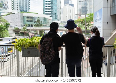 Hong Kong, China - June 21 2019: While anti-Government protestors surrounded the Hong Kong Police Headquarters in Wan Chai, three black-shirted protestors observed the situation from a walk bridge.