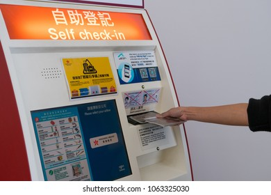 Hong Kong, China - March 19, 2018: Hand of young Asian woman at self service transfer area doing self check in kiosk machines at Terminal 1 at Hong Kong International Airport.