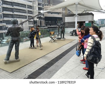 HONG KONG, CHINA - MARCH 2017: Tourists pose for camera at Avenue of Stars which is closed off for three years while its redevelopment and expansion is undertaken.