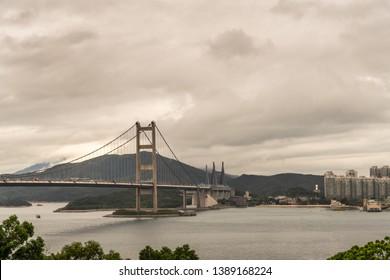 Hong Kong, China - March 7, 2019: Morning under dark rainy sky. Tsing Ma Bridge crossing gray Ma Wan Channel from Wok Tai Wan to Park Island. High rise buildings, dark hills on horizon.