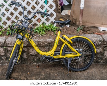 Hong Kong, China - March 8, 2019: Tai Po Market in New Territory. Yellow OFO bike for hire, to share, stands on side of market. Kotex, maker of feminine care products, sponsors.