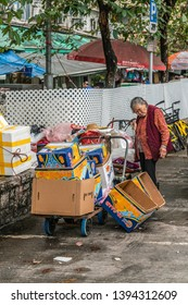 Hong Kong, China - March 8, 2019: Tai Po Market in New Territory. Older woman collects carton boxes. Market booths behind white fence.