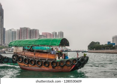Hong Kong, China - May 12, 2010: Green roofed brown wooden sampan on greenish waters of central Harbor. High rise buildings as background under silver sky.