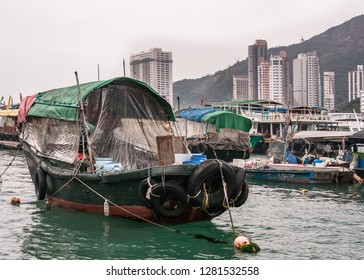 Hong Kong, China  - May 12, 2010: Closeup of Green and black wooden old houseboat in harbor. Sloops around, hill and tall highrise buildings on shore in background. All under silver sky.