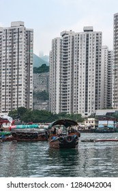 Hong Kong, China  - May 12, 2010: Brown wooden ferry sampan crosses the harbor with white tall apartment buildings on shore. Green hills in between. All under silver sky.