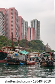 Hong Kong, China  - May 12, 2010: Brown wooden ferry sampan and group of houseboats and sloops docked in  harbor with white tall apartment buildings on shore. Silver sky.